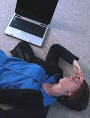 woman lying on the floor, her face in her hands beside a laptop