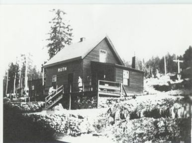 """Ruth Station. A fine picture of the Ruth station from the early days. Note the hoop on the verandah near the center of the picture. This was used to pass train orders to the engine crew, as the train was passing by. Thanks to Joe Smuin, author of the book, """"Kettle Valley Railway, Mileboards"""", who has the original of this photo."""