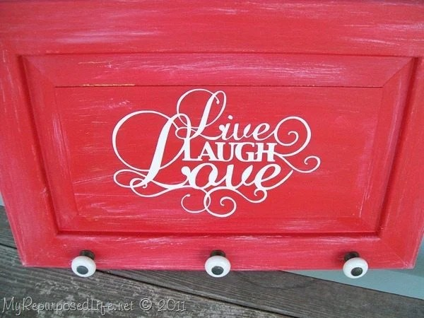 How to make an easy live laugh love sign out of an old microwave cabinet door. Tips on painting and using repurposed hardware knobs. #MyRepurposedLife #repurposed #Cupboard #door #livelaughlove #sign via @repurposedlife