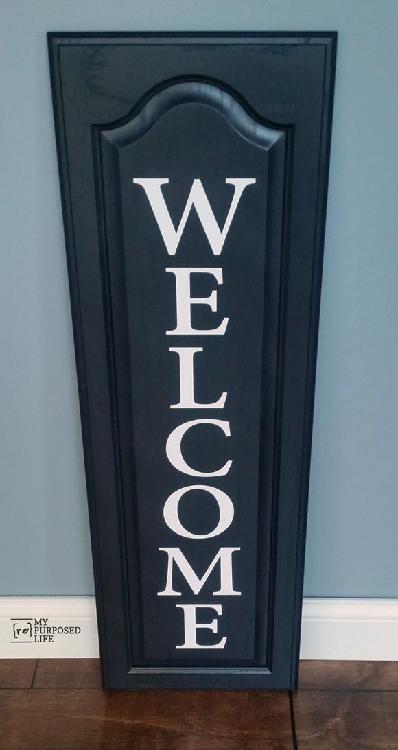 My Repurposed Life black and white WELCOME sign using an old cabinet door and vinyl