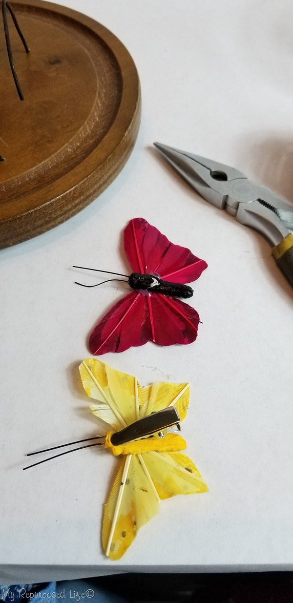 remove clips from butterflies for repurposed cloche butterfly garden