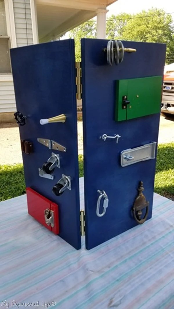 two large boards hinged together to make toddler busy board