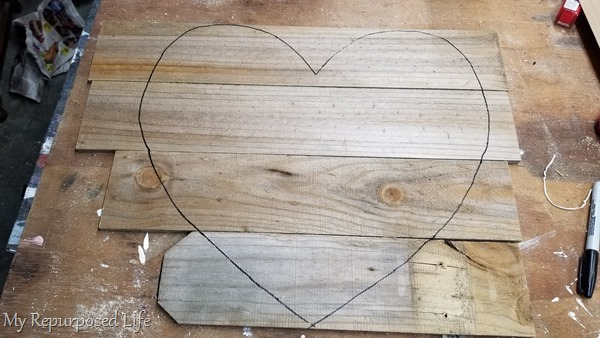 trace paper heart pattern on reclaimed wood fencing