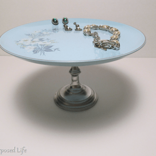 plate stand with vintage jewelry