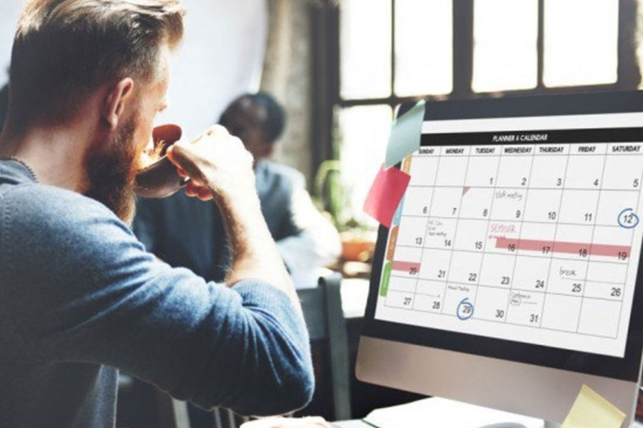 Man sipping coffee looking at a calendar