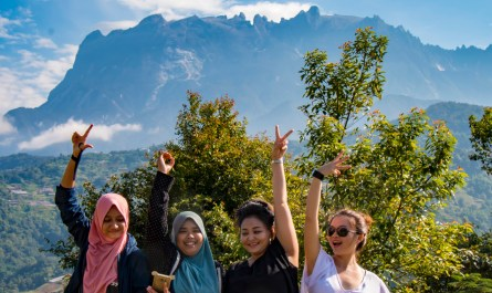 Four girls taking group photo with Mount Kinabalu
