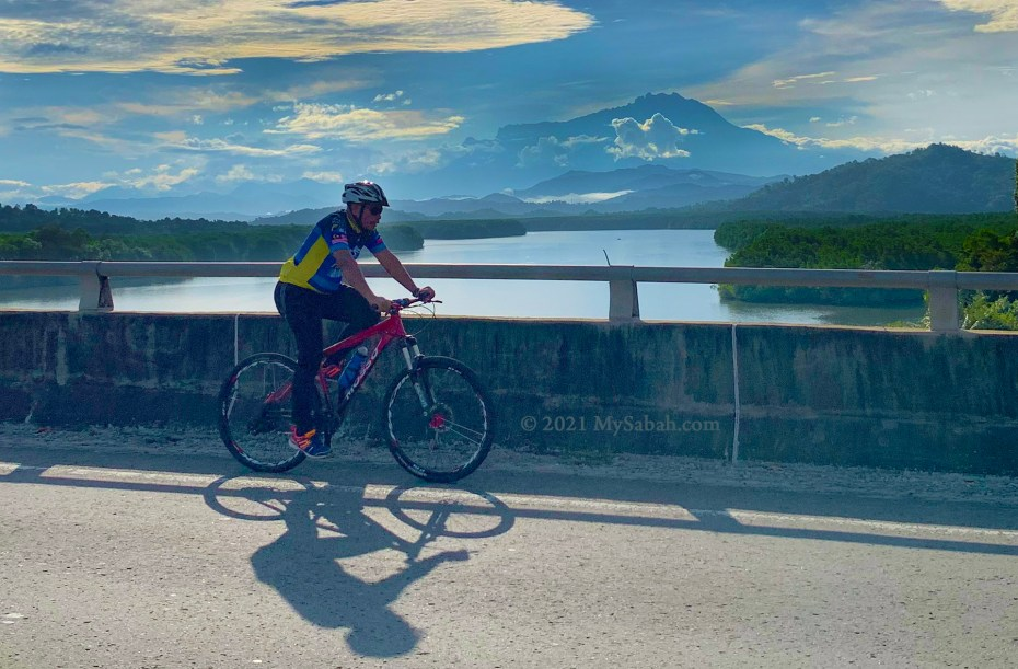 Cycling on Mengkabong River Bridge with the view of Mount Kinabalu