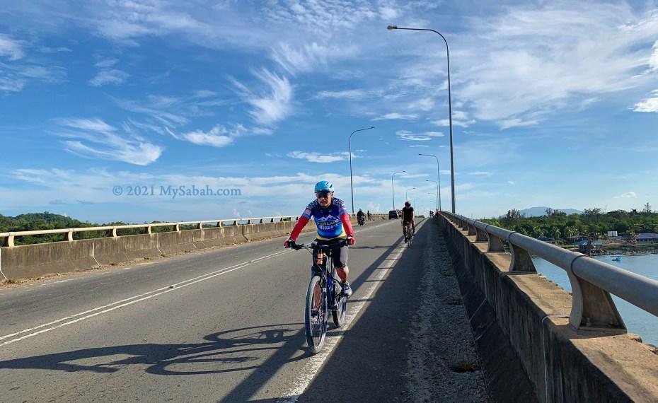 Cyclists crossing the Mengkabong River Bridge