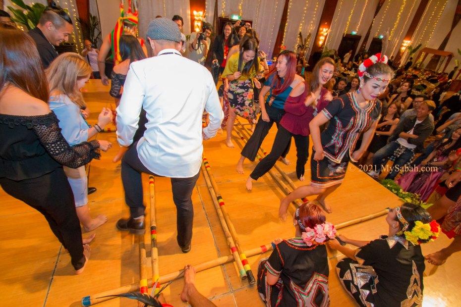 Tourists try Magunatip bamboo dance