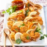 coconut shrimp garnished with lemon slices and cilantro, with a spicy apricot dipping sauce