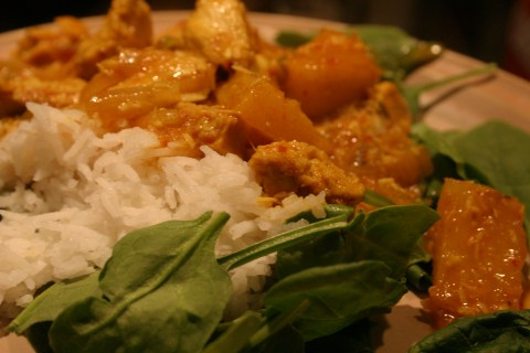 Pineapple coconut chicken curry on rice and spinach
