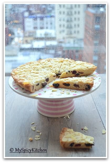 Sliced cranberry almond wedges on a cake stand