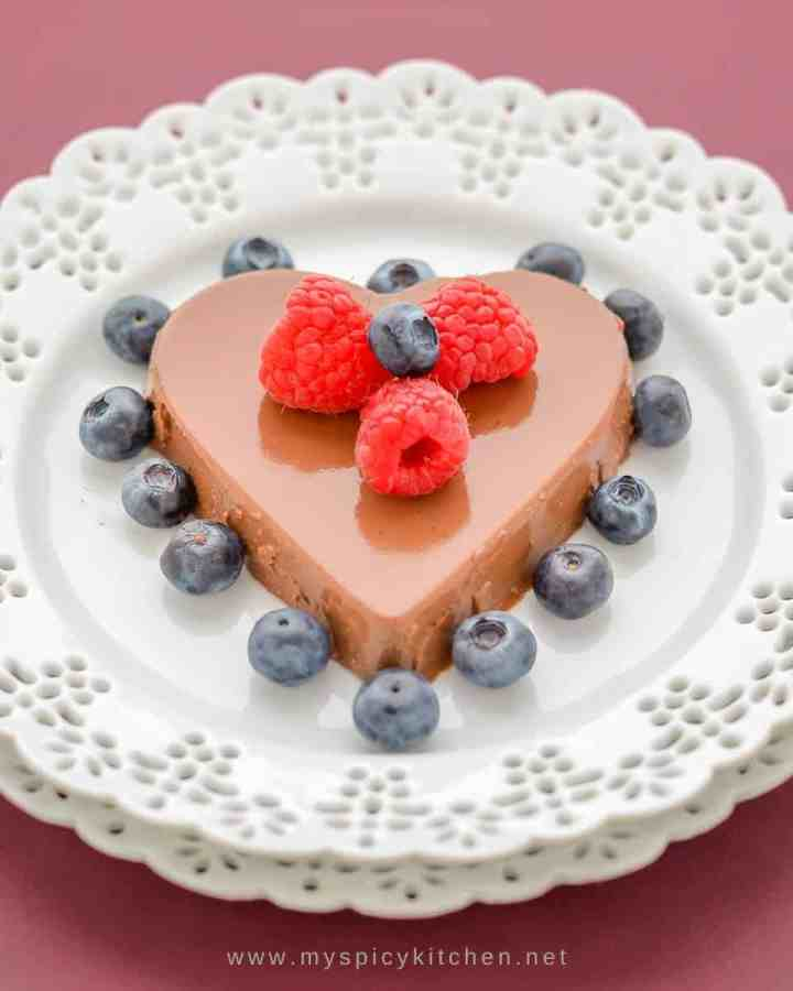 Heart shaped mocha panna cotta garnished with raspberries and blueberries