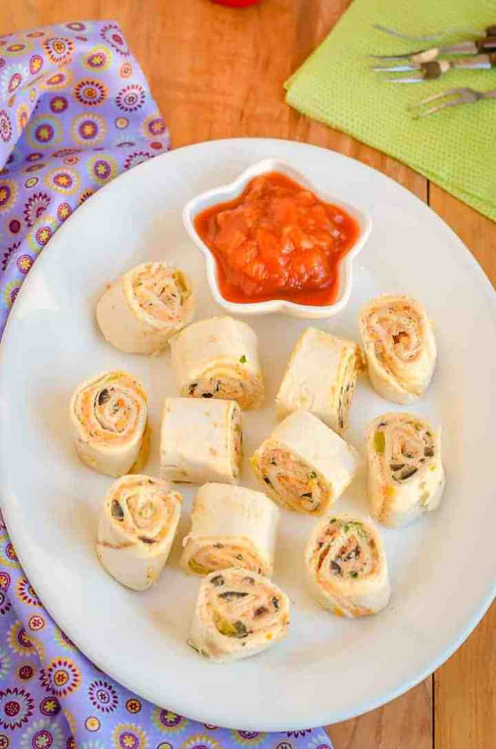 A platter of Fiesta pinwheels and a bowl of salsa