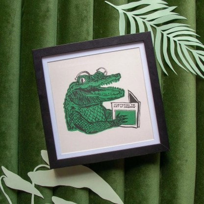 "Risograph framed art print with an illustration of an alligator smiling while reading a book titled ""Mastering the art of sunbathing"""
