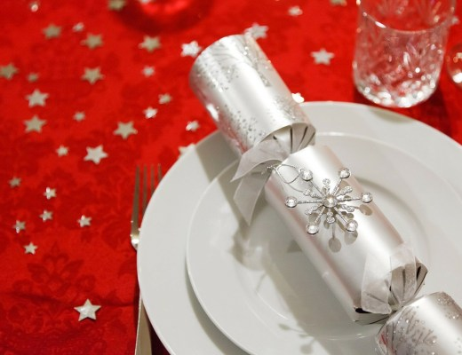 A Silver Christmas cracker placed upon a white dinner plate