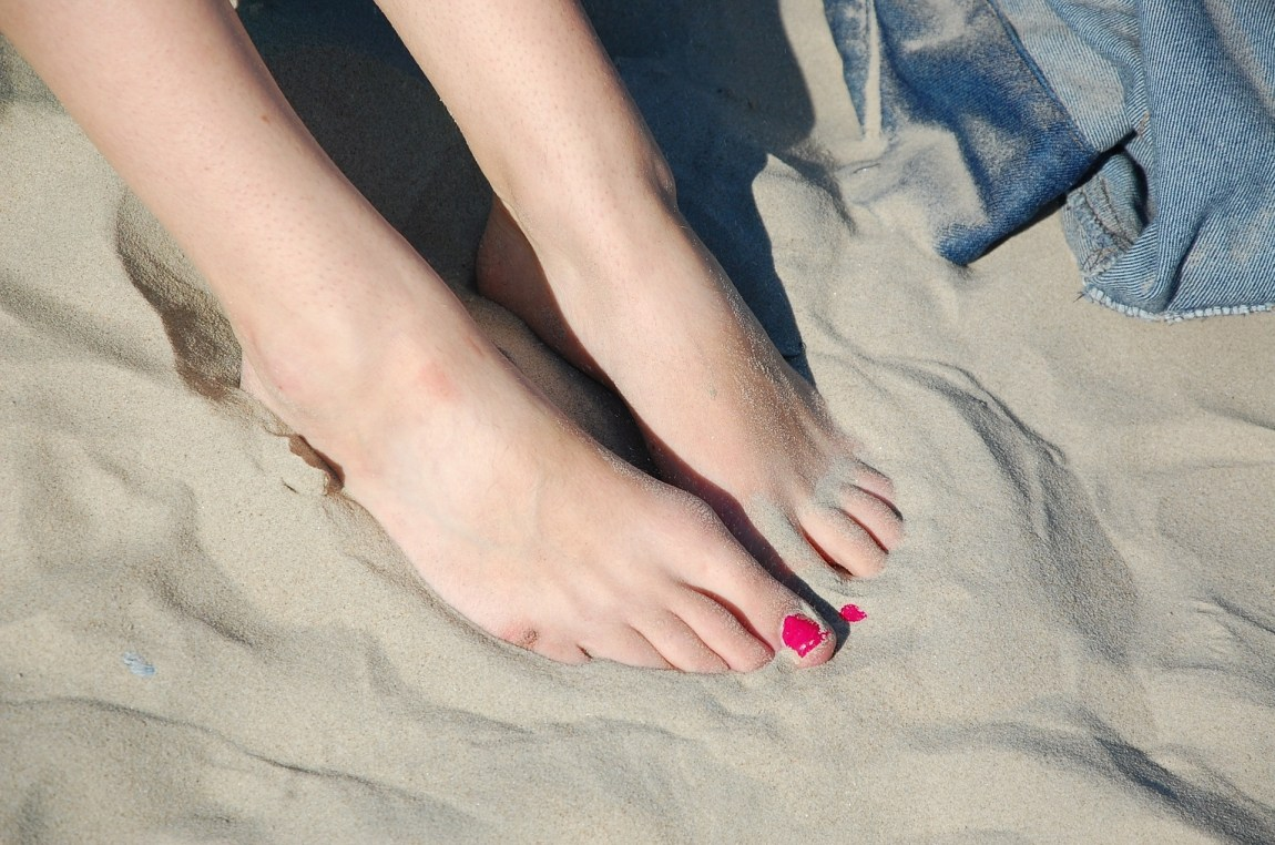 ladies feet in the sand. her toe nails are painted bright pink