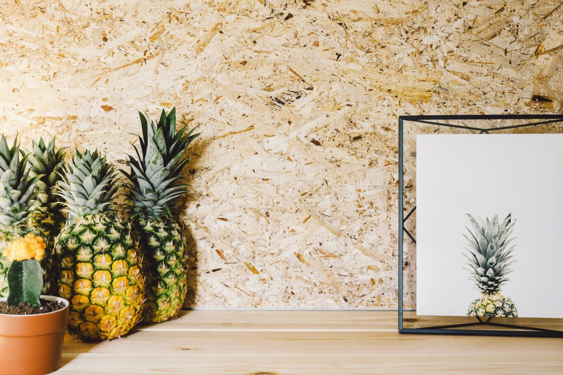 four pineapples next to a cactus plant and picture frame with a pineapple print inside it.