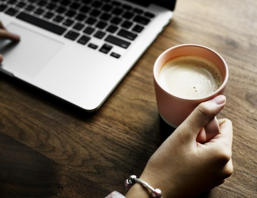 A woman sat to a table with a laptop and a cup of coffee