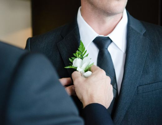 A groom having a white button hole flower added to his black suit on his wedding day