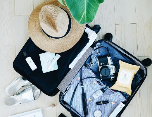 an open suitcase containing clothes and a hat, next to it is a note book, camera and passport