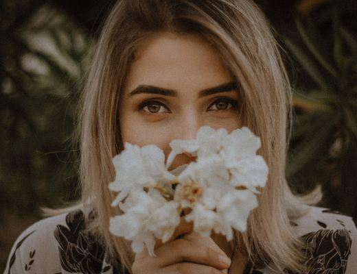 A woman with half her face hidden by a bunch of white flowers