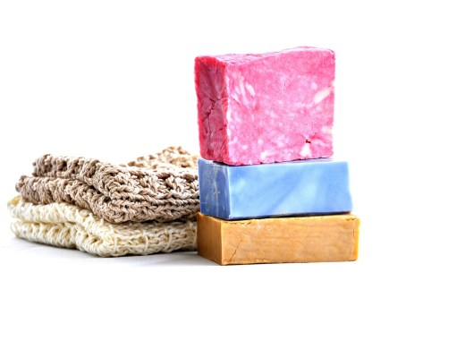 two bars of handmade soap next to two folded handmade garments
