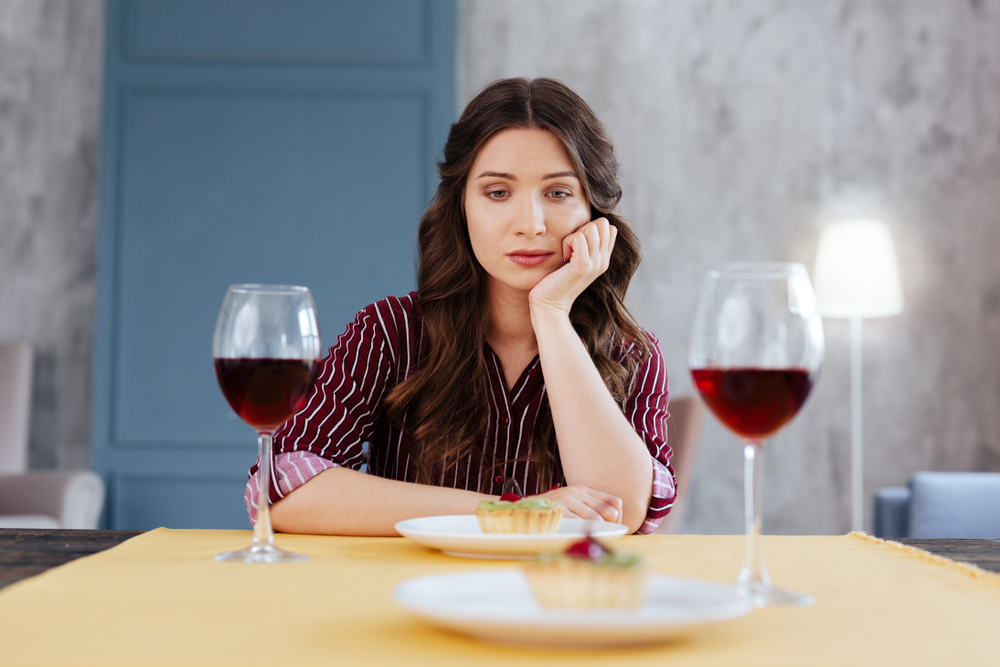 A woman sat at a table with two meals and two half full wine glasses in front of her. She looks fed up as she has her chin rested on her hand