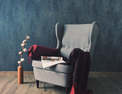 A grey highbacked armchair on a wooden floor with a blue wallpapered wall in the background
