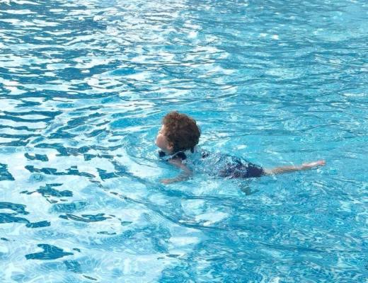 a little boy swimming in a pool