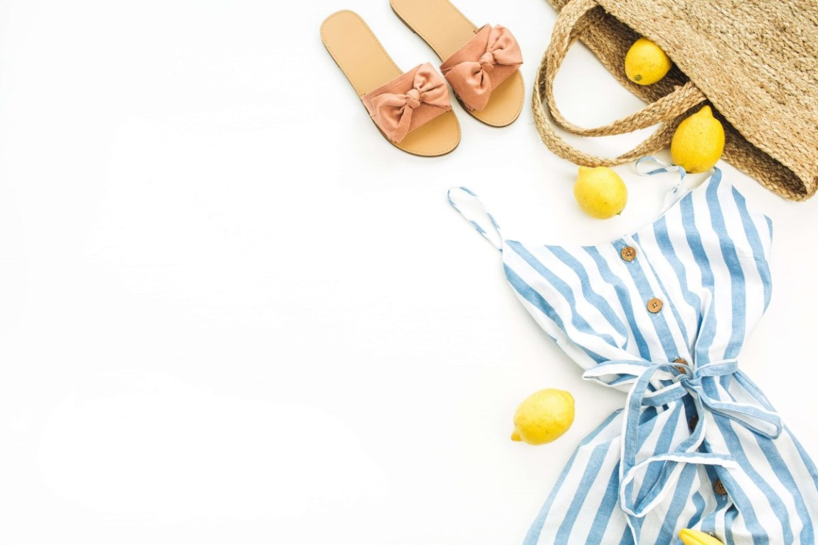 a blue and white striped dress next to a pair of brown sandals and a beach bag