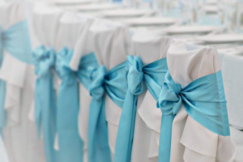 white chair covers with blue ribbon sashes