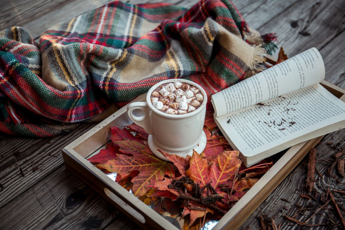 mug of hot chocolate on a tray with a book, next to a blanket on a wooden table