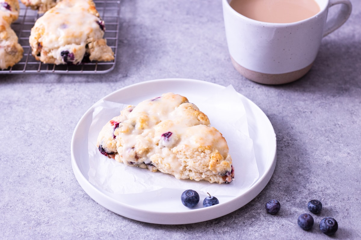 Angled view of a lemon blueberry scone on a plate surrounded by scattered fresh blueberries with a mug of coffee and more scones in the background on a light grey surface.