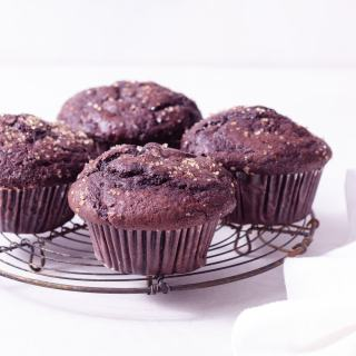 Straight on shot of Double Chocolate Chip Muffins on a wire rack next to a dish cloth on a white surface.