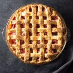 Strawberry Rhubarb Pie with lattice crust on dark grey background