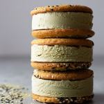 Straight on shot of a stack of matcha green tea ice cream sandwiches with sesame tahini cookies on a light grey surface surrounded by black and white sesame seeds and matcha powder.