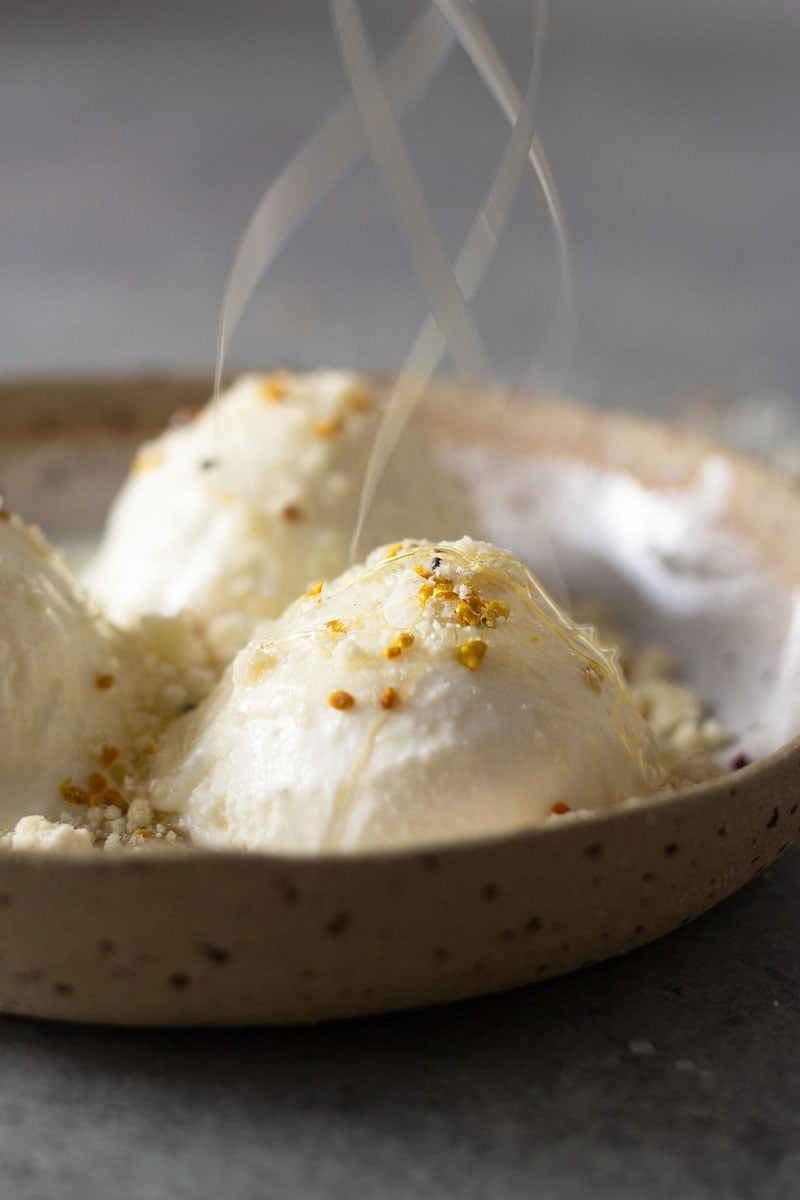 Straight on shot of a rustic ceramic bowl filled with milk ice cream, milk powder crumble, bee pollen and acacia honey with honey drizzling down on a light grey, textured surface.
