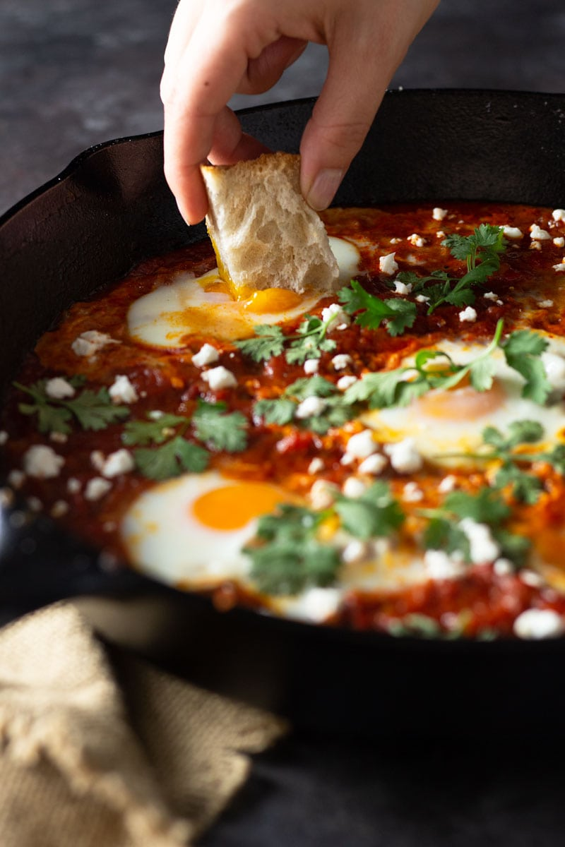 3/4 angled shot of a cast iron pan of shakshuka (baked eggs in a spiced tomato sauce) with harissa paste, feta cheese and cilantro with a hand dipping a piece of bread into the yolk on a dark grey textured surface next to a tan dish towel.