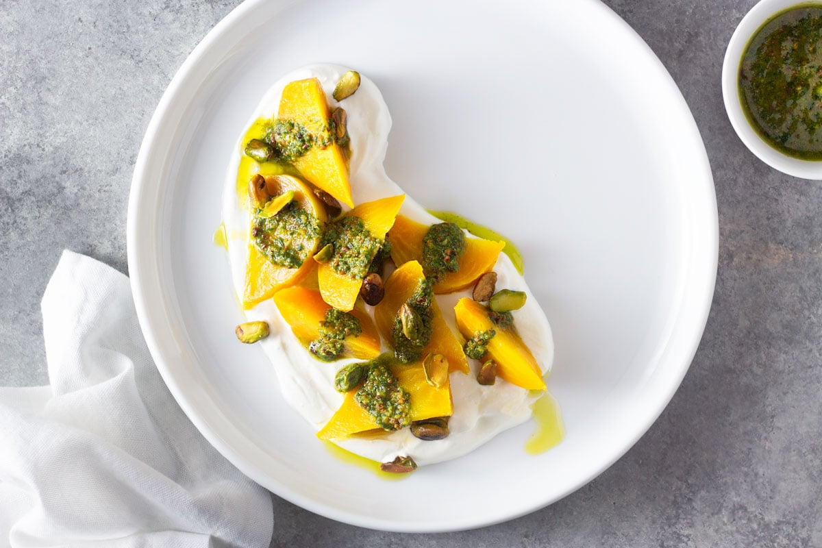 Overhead shot of a white plate of wedges of golden beets on top of a goat cheese yogurt spread, topped with pistachio pesto and toasted whole pistachios on a light grey, textured surface surrounded by a small bowl of pesto and a white dish towel.