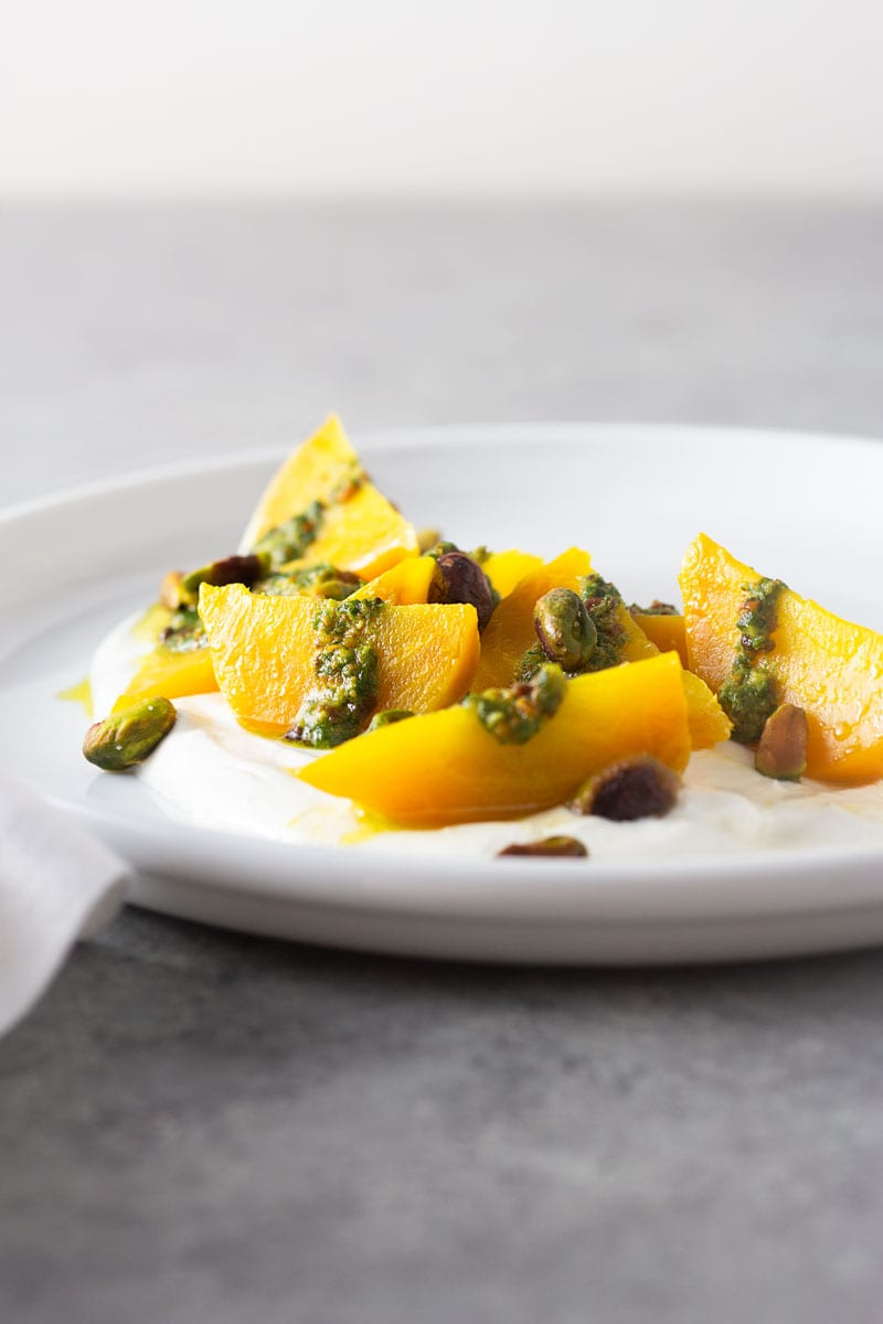 Straight on shot of a white plate of wedges of golden beets on top of a goat cheese yogurt spread, topped with pistachio pesto and toasted whole pistachios on a light grey, textured surface.
