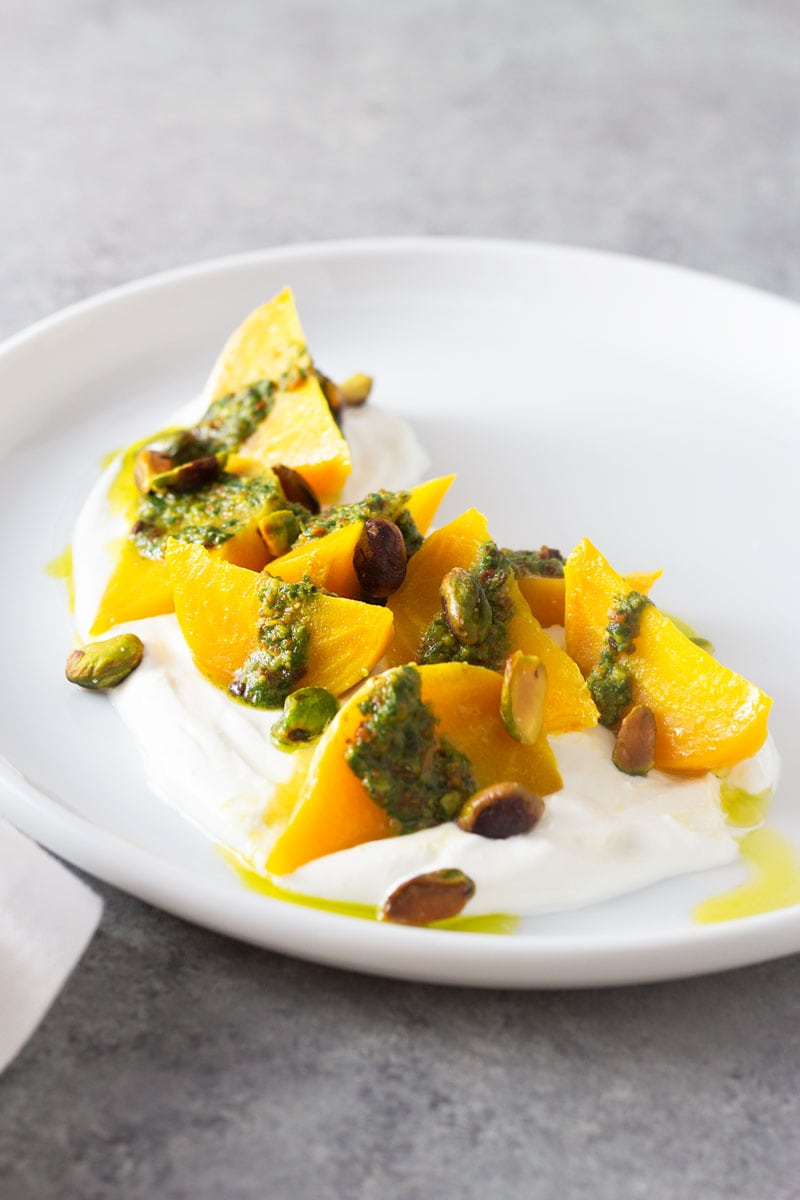3/4 angled shot of a white plate of wedges of golden beets on top of a goat cheese yogurt spread, topped with pistachio pesto and toasted whole pistachios on a light grey, textured surface.