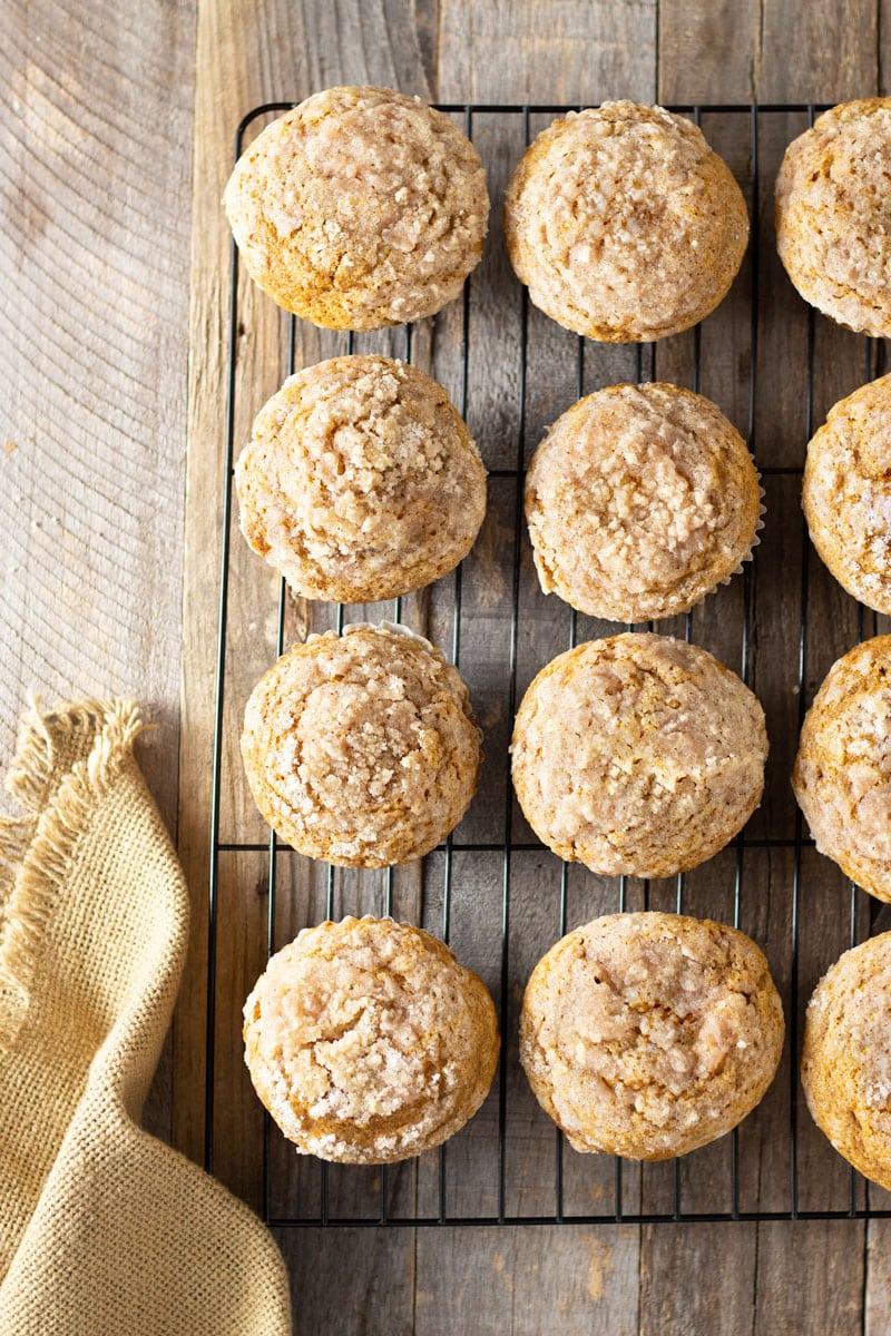 Overhead shot of a rack of Pumpkin Cream Cheese Streusel Muffins on a grey wood surface surrounded by a tan cloth.