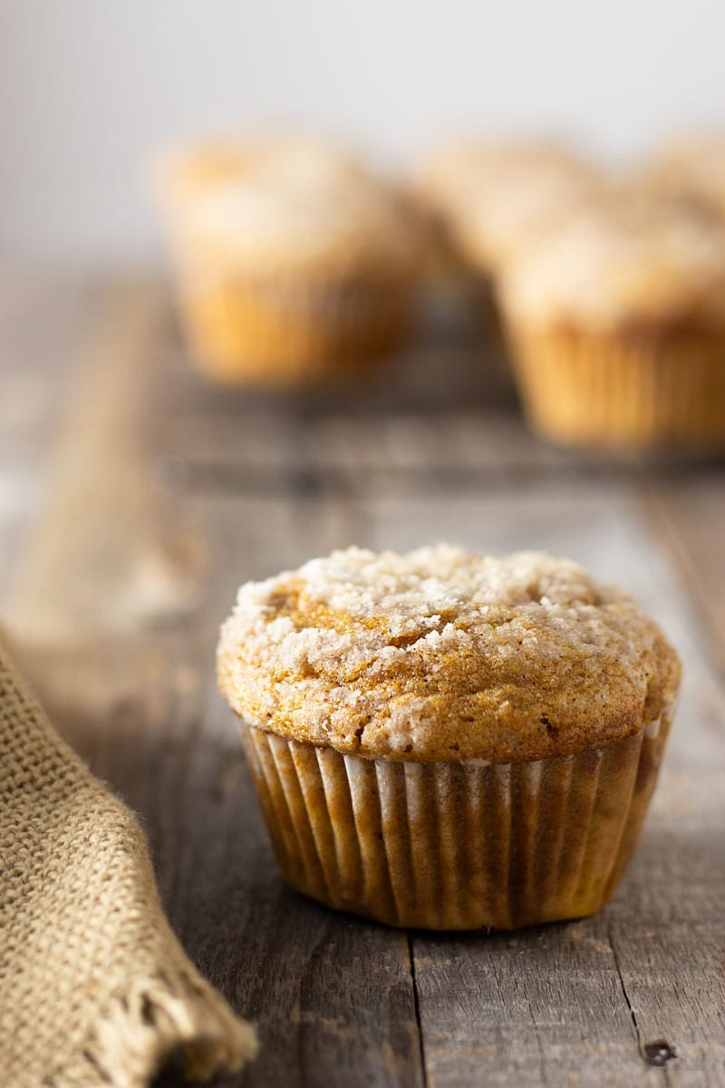 Straight on shot of a Pumpkin Cream Cheese Streusel Muffin on a grey wood surface surrounded by a tan cloth with muffins on a cooling rack in the background.