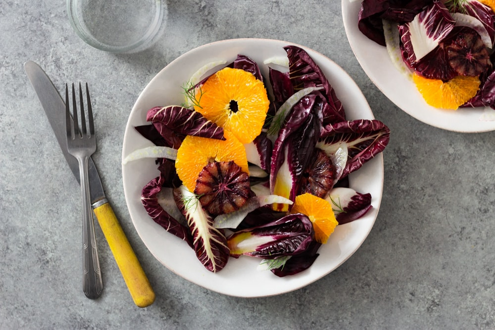 Overhead view of an Orange and Fennel Salad with Radicchio, blood orange, fennel fronds and a sherry vinaigrette on a white plate surrounded by another plate of salad, a fork, a knife and a glass of water on a grey, textured surface.