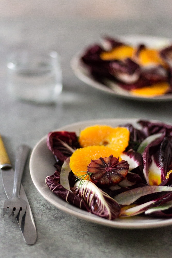 3/4 angled view of an Orange and Fennel Salad with Radicchio, blood orange, fennel fronds and a sherry vinaigrette on a white plate next to a fork and a knife with a glass of water and another salad in the background on a grey, textured surface.