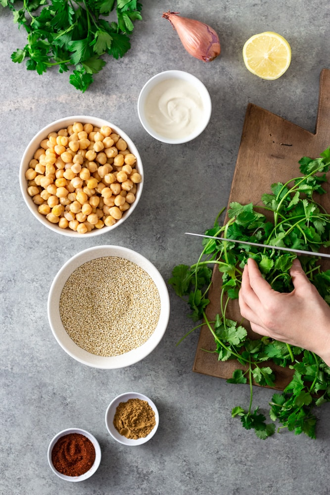 Overhead view of prep for a salad. Cilantro is being cut on a wooden cutting board. There is fresh parsley, a shallot, half of a lemon, a bowl of tahini yogurt, a bowl of chickpeas, a bowl of raw quinoa, and bowls of cumin and paprika on a light grey textured surface.