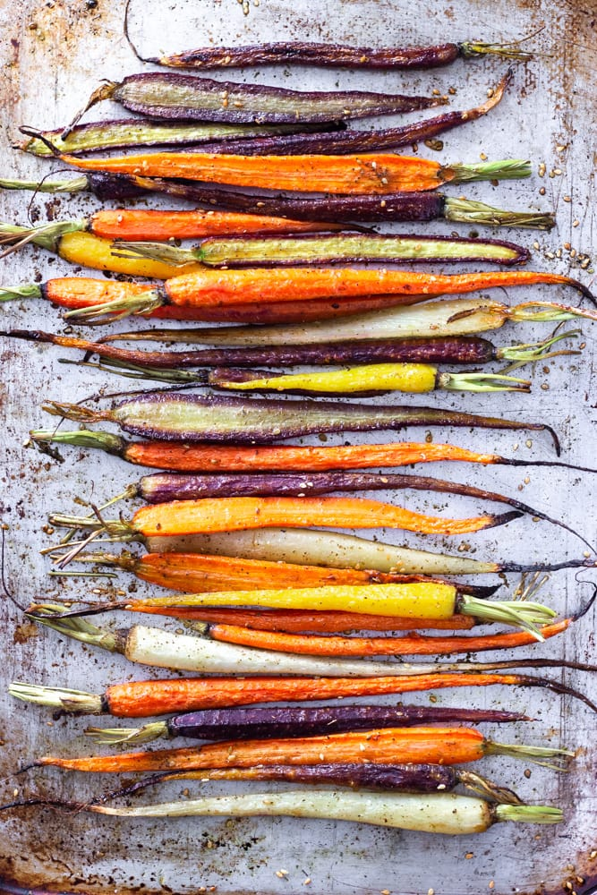 Overhead shot of mixed colored roasted heirloom carrots on a sheet tray.
