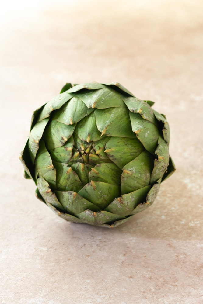 Straight on shot of a raw globe artichoke on a beige textured surface.