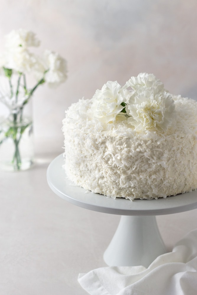 Angled view of a coconut layer cake with Swiss meringue buttercream on a cake stand with a vase of white carnation flowers in the background with a cream colored surface and light textured background.